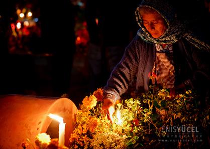 Yaşlı bir Meksikalı kadın aile yakınlarının mezarında mum yakarken.