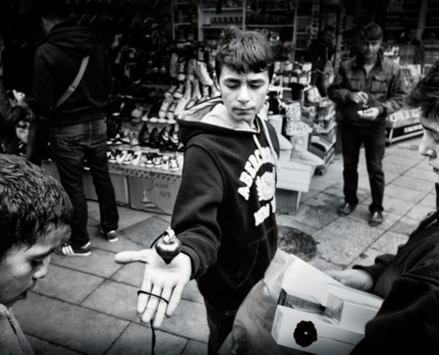 A young boy selling spinning tops in Istanbul streets.