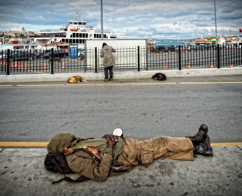 A homeless is sleeping on a sidewalk of a busy road in Eminönü, Istanbul.