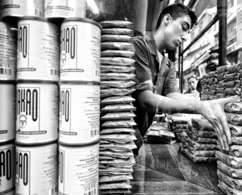 A young employee aligning the Turkısh Coffee packages for a more tempting showcase for customers.